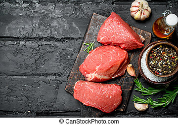 Raw meat. Pieces of beef with spices and herbs.