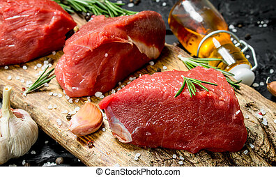 Raw meat. Pieces of fresh beef with spices, garlic and rosemary.