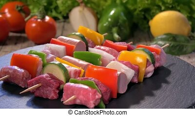 a table spread with raw meat skewers on a stone plate rotating and fresh vegetables