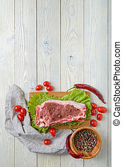 raw meat with ingredients on a wooden background