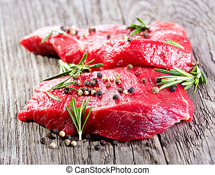 raw meat with rosemary on wooden table