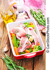 raw meat with vegetables in bowl and on a table