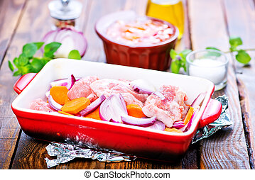 raw meat with vegetables in the bowl and on a table