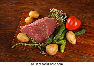 Raw meat with vegetables on a wooden table for a delicious...