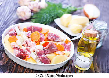 raw meat with vegetables on the white plate