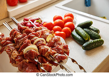 raw meat with vegetables threaded onto a skewer for roasting...