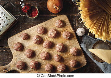 Raw meatball for spaghetti on the wooden board top view