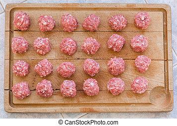 Raw meatballs on the cutting board