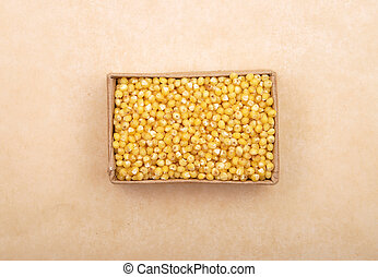 Raw millet in carton and on brown background