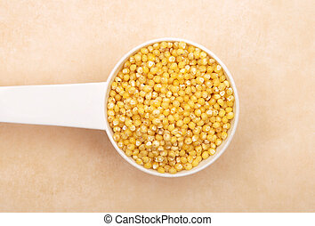 Raw millet in measuring spoon on brown background