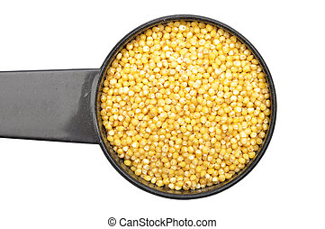 Raw millet in measuring spoon on white background