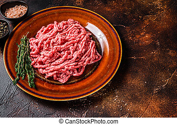 Raw mince angus wagyu beef, ground meat with herbs on a plate. Dark background. Top view. Copy space