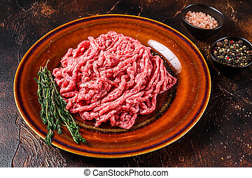 Raw mince angus wagyu beef, ground meat with herbs on a plate. Dark background. Top view