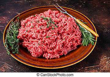 Raw mince beef and lamb meat on a rustic plate with herbs. Dark background. Top view