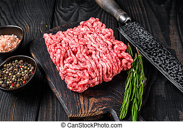 Raw mince lamb, ground meat with herbs and spices on a wooden cutting board. Black wooden background. Top view