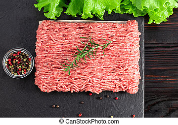 raw minced meat and spices on dark background, top view