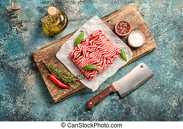 Raw minced meat with olive oil and seasoning on paper over ...