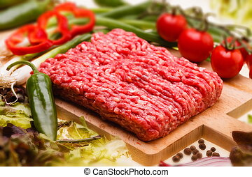 raw minced meat with vegetables on wooden board