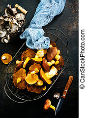 raw mushrooms in basket and on a table