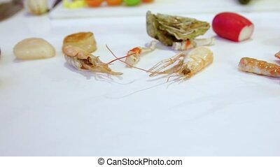 Raw octopuses and raw sea scallops on white table, cam moves to the left, closeup