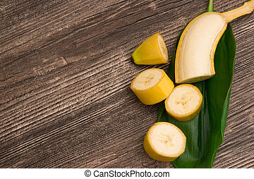 Raw organic yellow bananas with green leaf on wooden background
