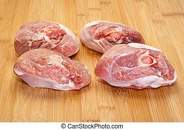 ossobuco (bone-in lamb shank steaks) on a wooden chopping board
