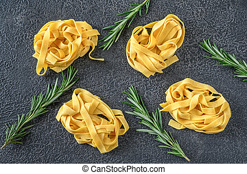 Raw pappardelle - flat Italian pasta noodles with fresh rosemary