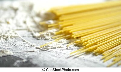 raw pasta cappellini, closeup lie in white flour on a wooden...