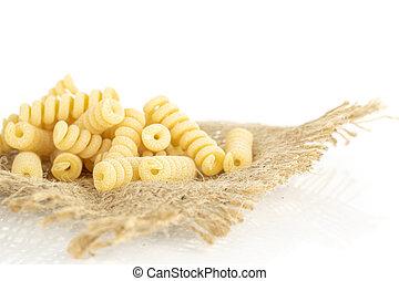 Lot of whole fresh raw pasta fusilli bucati closeup on jute cloth isolated on white background