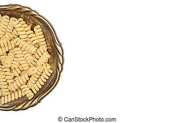 Lot of whole fresh raw pasta fusilli bucati copyspace in old iron bowl flatlay isolated on white background