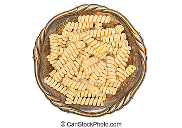 Lot of whole fresh raw pasta fusilli bucati in old iron bowl flatlay isolated on white background