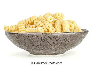 Lot of whole fresh raw pasta fusilli bucati on grey ceramic plate isolated on white background
