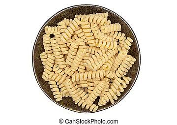 Lot of whole fresh raw pasta fusilli bucati on grey ceramic plate flatlay isolated on white background