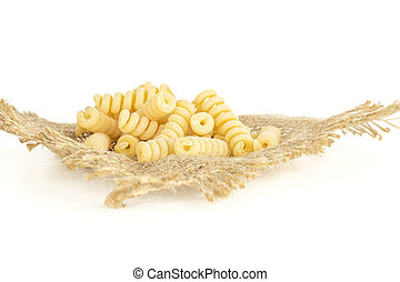 Lot of whole fresh raw pasta fusilli bucati on jute cloth isolated on white background