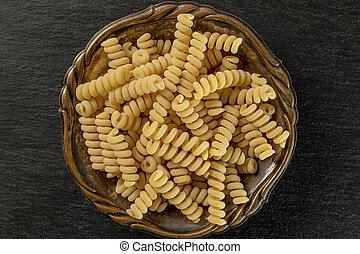 Lot of whole fresh raw pasta fusilli bucati in old iron bowl flatlay on grey stone