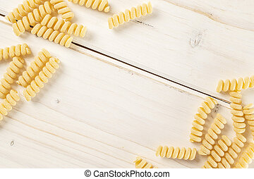 Lot of whole fresh raw pasta fusilli bucati copyspace in middle flatlay on white wood