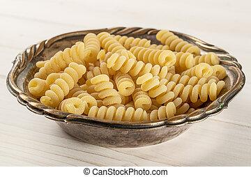 Lot of whole fresh raw pasta fusilli bucati in old iron bowl on white wood