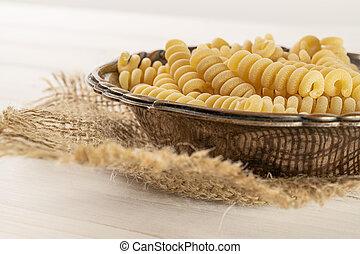 Lot of whole fresh raw pasta fusilli bucati in old iron bowl on jute cloth on white wood