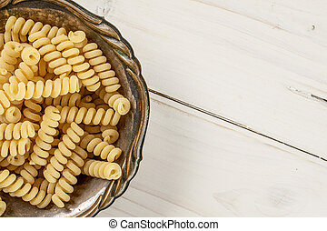 Lot of whole fresh raw pasta fusilli bucati in old iron bowl flatlay on white wood