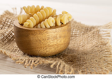 Lot of whole fresh raw pasta fusilli bucati in wooden bowl on jute cloth on white wood