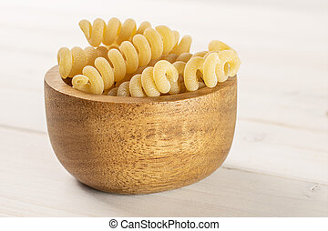 Lot of whole fresh raw pasta fusilli bucati in wooden bowl on white wood