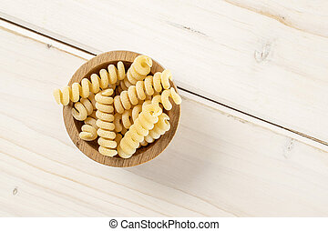 Lot of whole fresh raw pasta fusilli bucati in wooden bowl flatlay on white wood