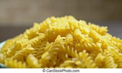 raw pasta. Fusilli, close-up. drop on a blue plate - raw...