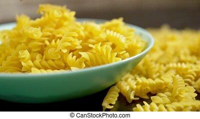 raw pasta. Fusilli, close-up. raw pasta. falls in a blue...