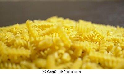 raw pasta. Fusilli, closeup fall on a wooden table, - raw...