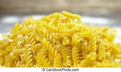 raw pasta fusilli, closeup lie in white flour on a wooden...