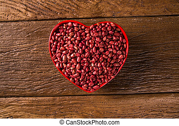 Raw peanuts in heart bowl.