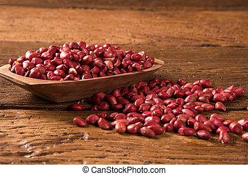 Raw peanuts in wood bowl.
