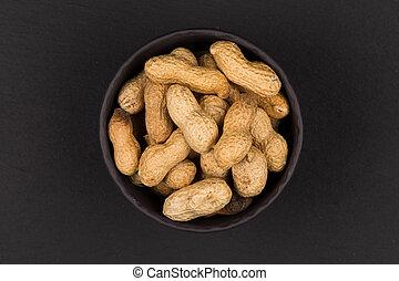 Raw peanuts shells in bowl