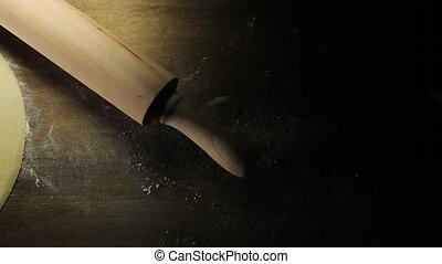 Raw pizza dough, a rolling pin on a wooden surface. Camera...